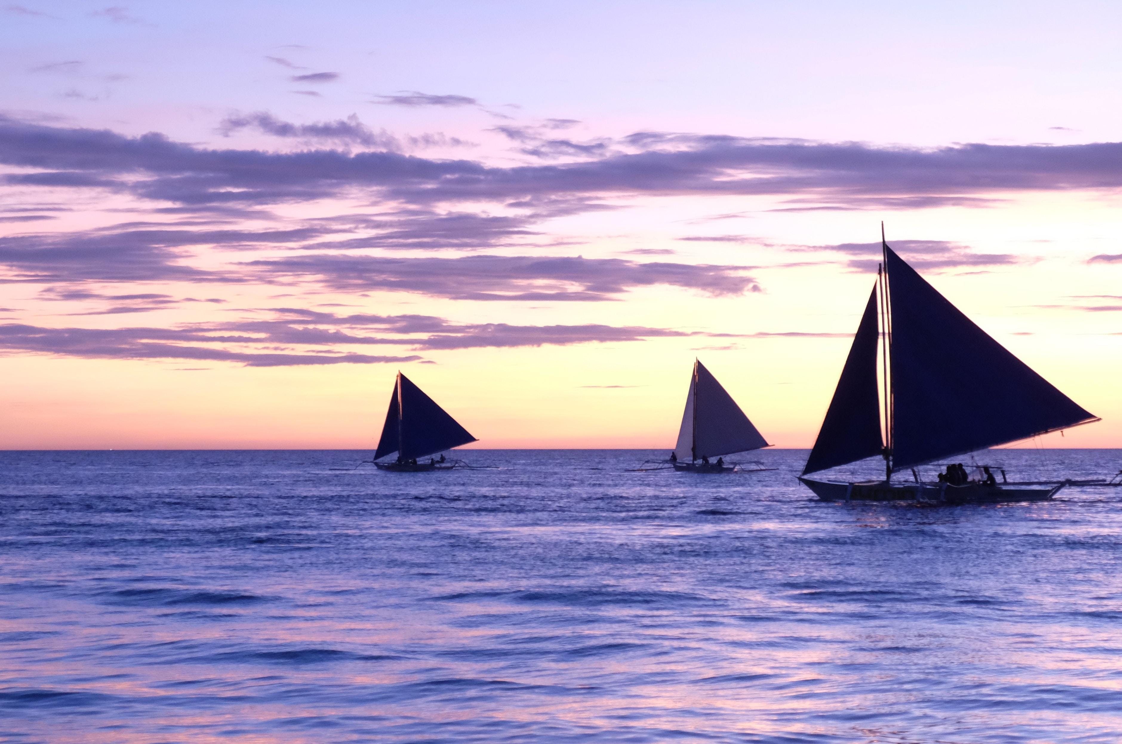 three sailboats on sea