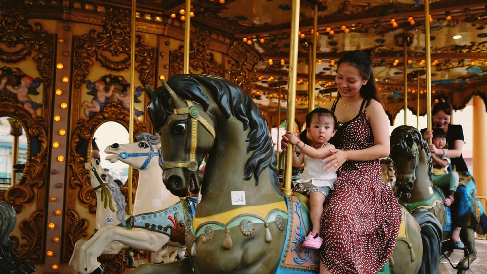 child and woman riding horse carousel