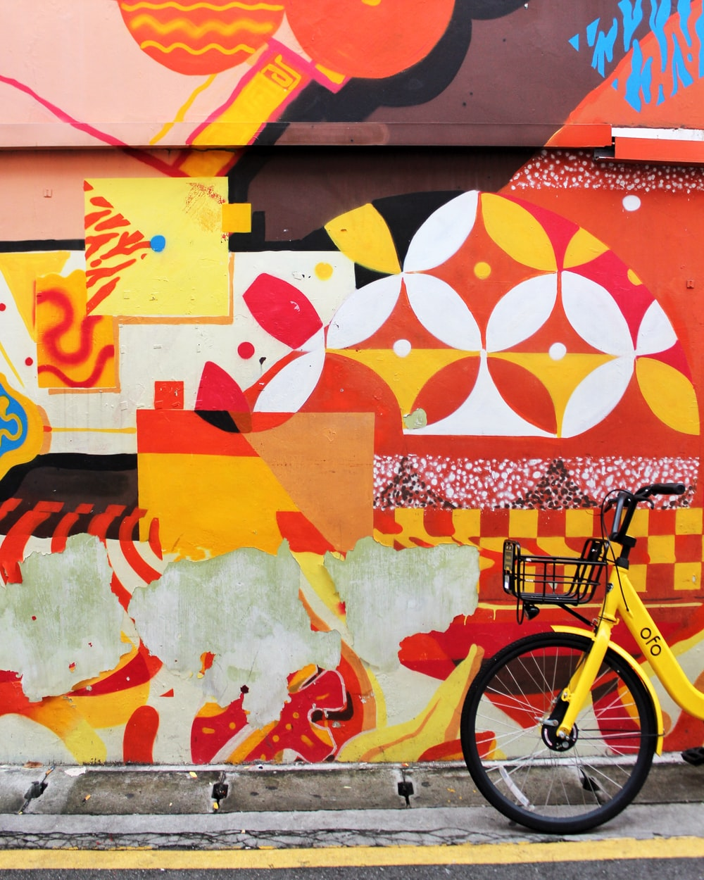 yellow city bike beside multicolored wall