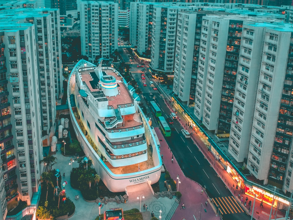 white boat building surrounded with high-rise buildings