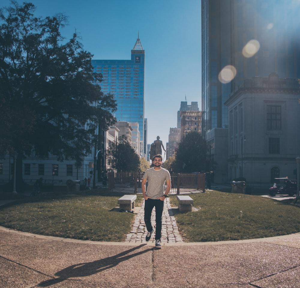 man wearing gray crew-neck shirt standing across gray statue