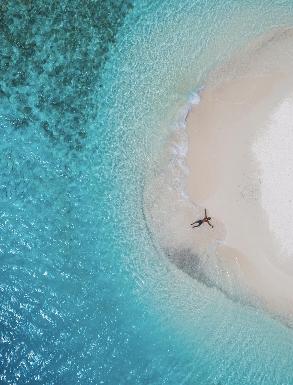 person lying on seashore