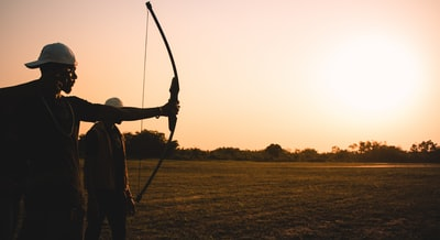 man holding bow during daytime bow zoom background