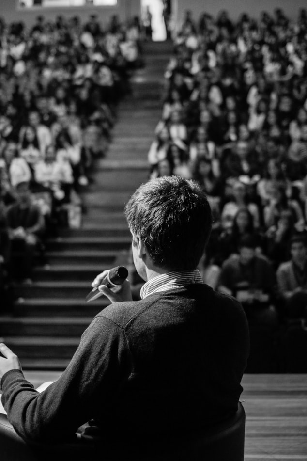 Black and white photo of a person speaking to a crowded auditorium