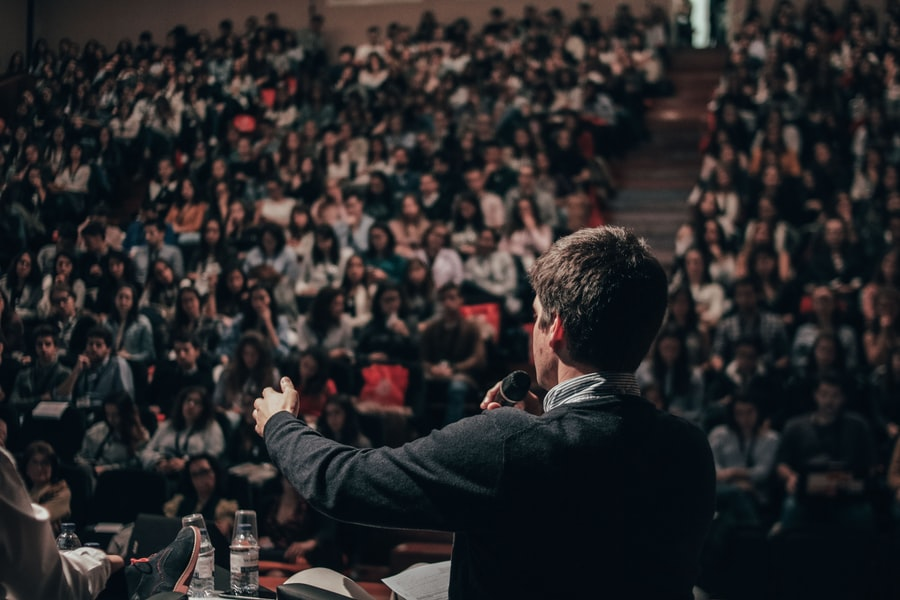 A lecturer stands at a podium holding a microphone, giving a speech to an auditorium full of other people.