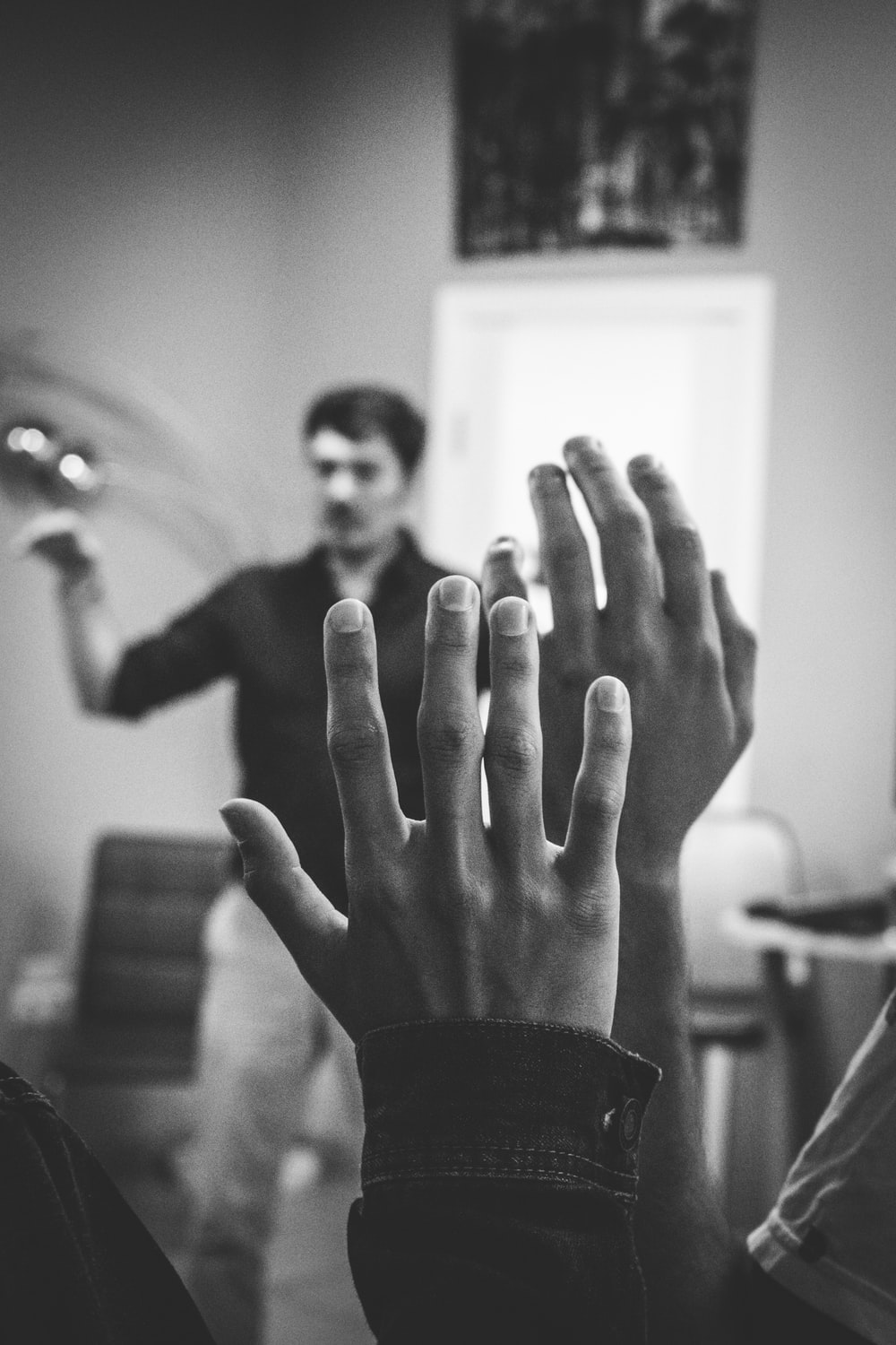 grayscale photography of two people raising their hands