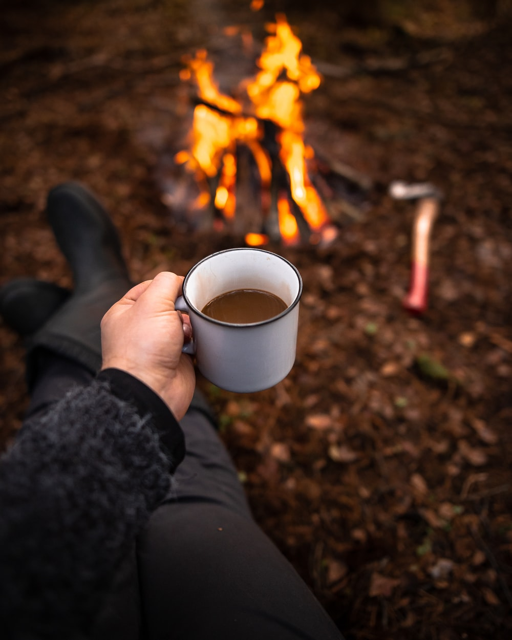 person holding white mug on front of bonfire