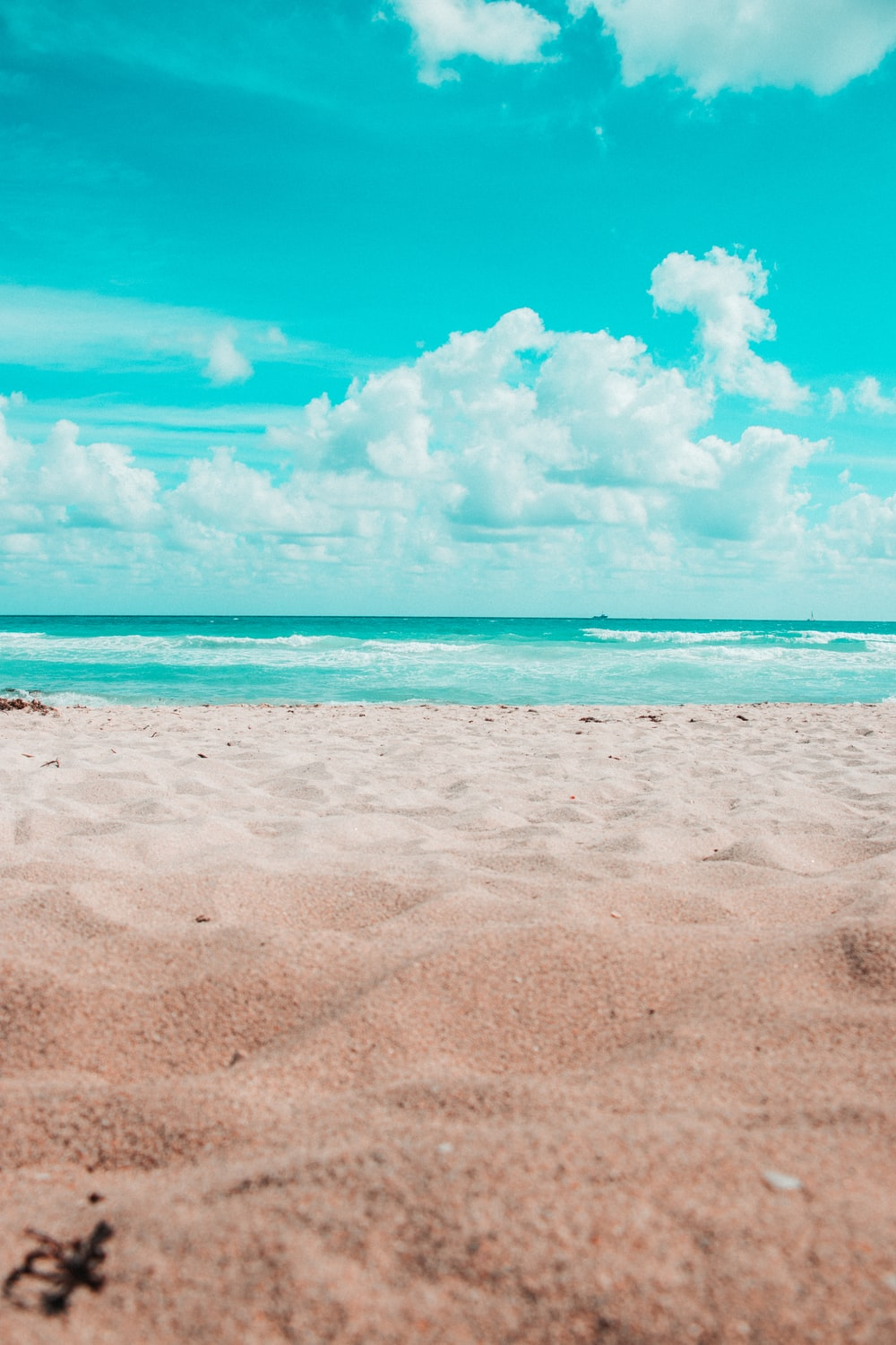 beach under blue sky and white clouds during daytime