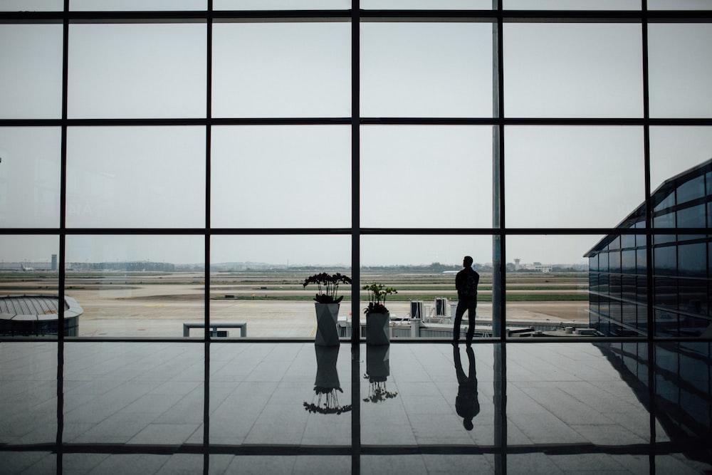 man standing near glass window