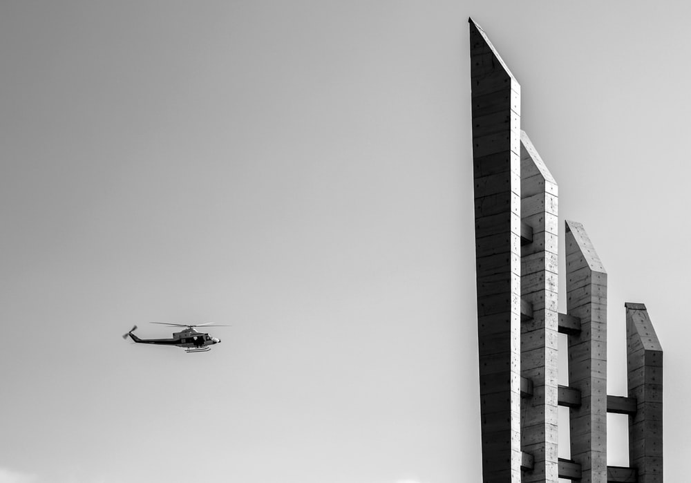 grayscale photography of helicopter near the building