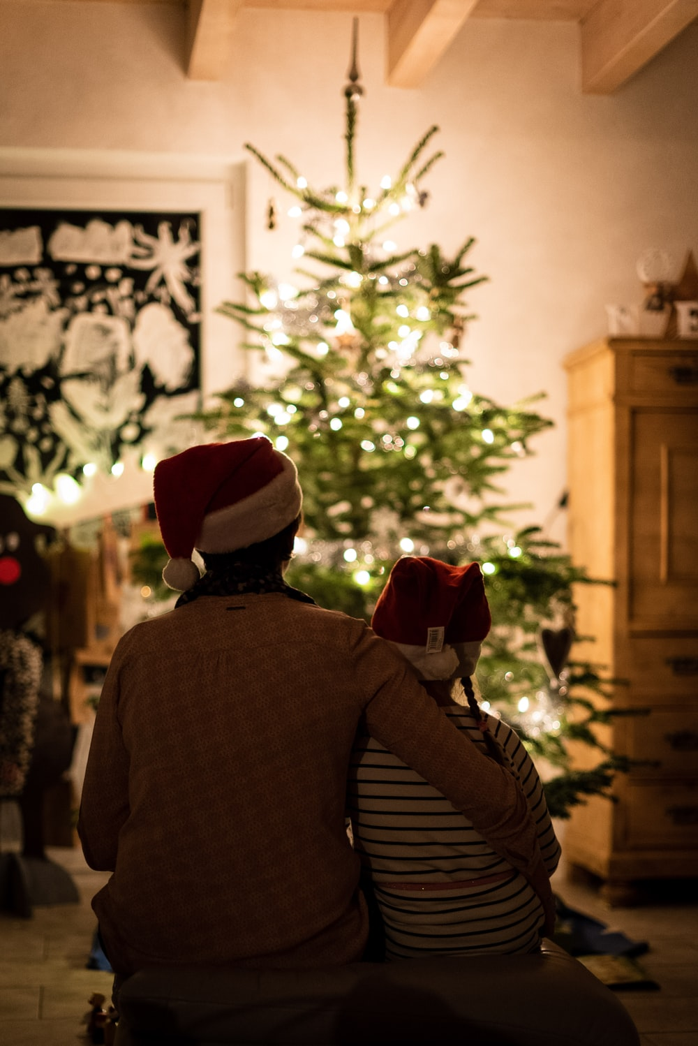 selective focus photography of girl an woman hugging each other in front of christmas tree