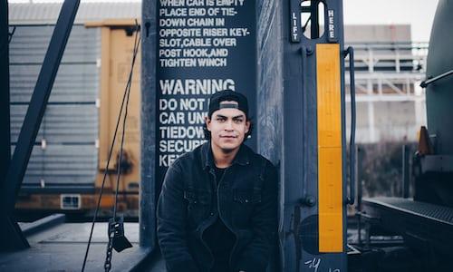 A man sitting under a warning sign.