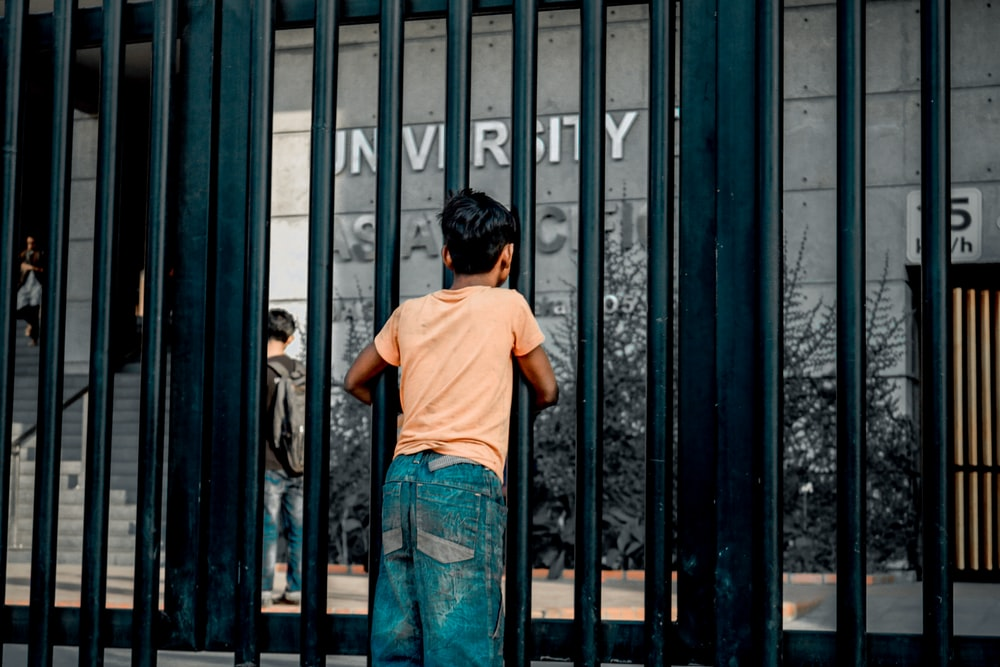 boy standing beside glass building