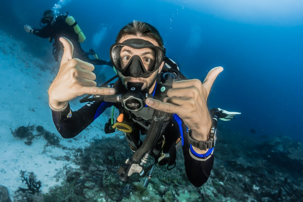 man underwater making hand signs