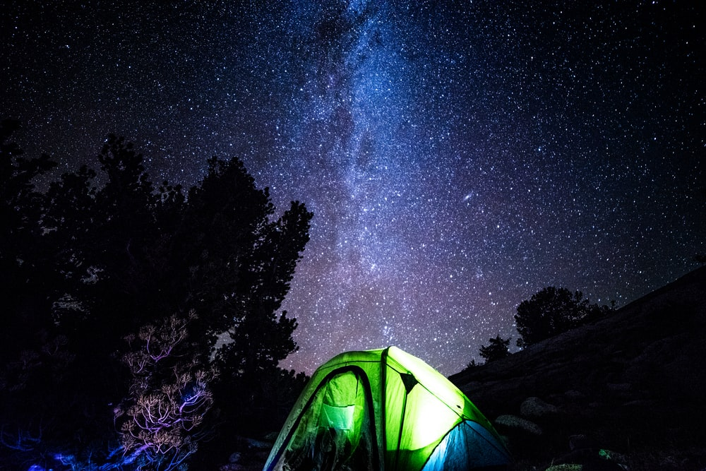 lights inside closed green and blue tent under starry sky