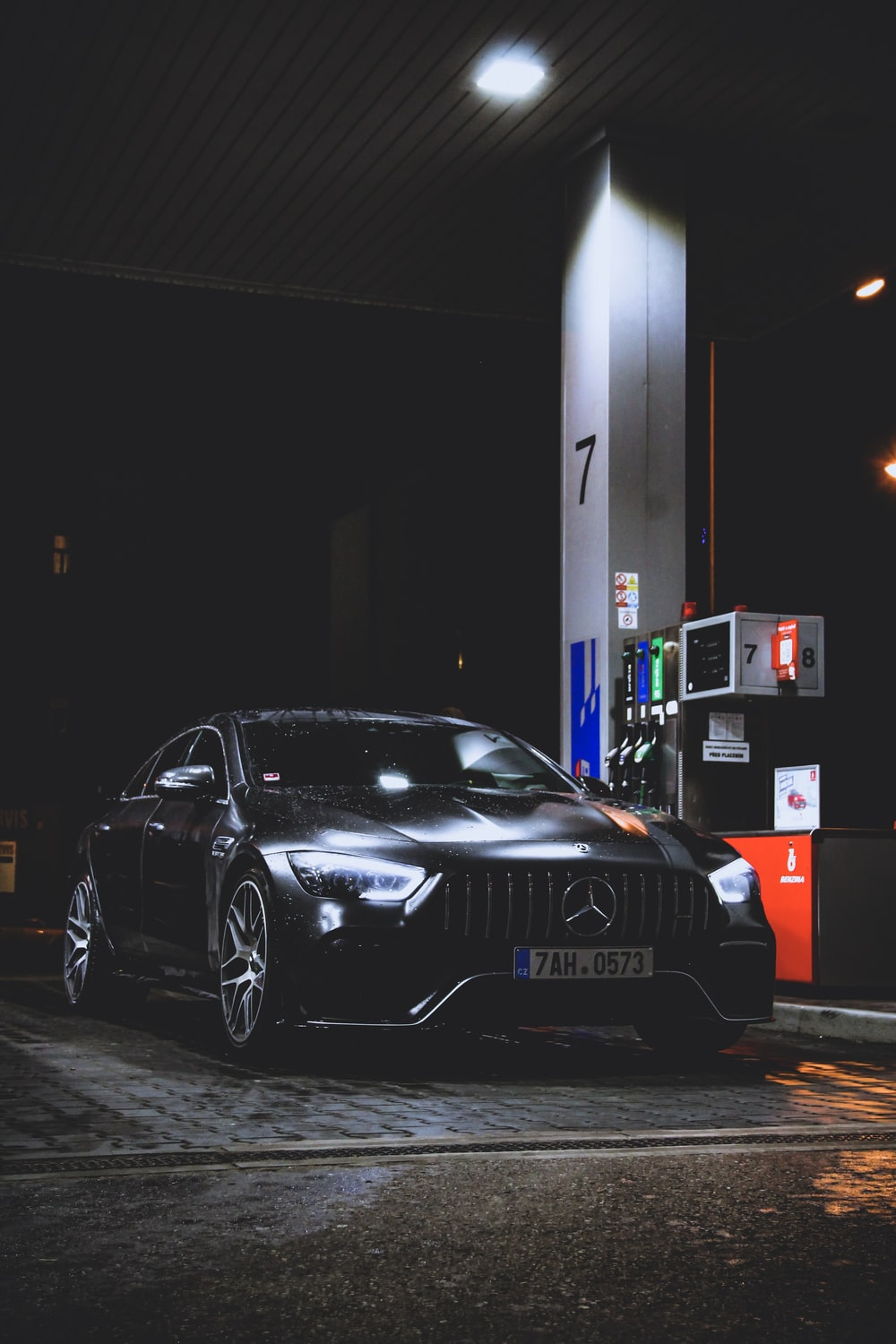 black Mercedes-Benz car at gas station at night