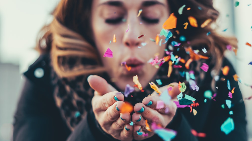 woman blowing paper strips in selective focus photography