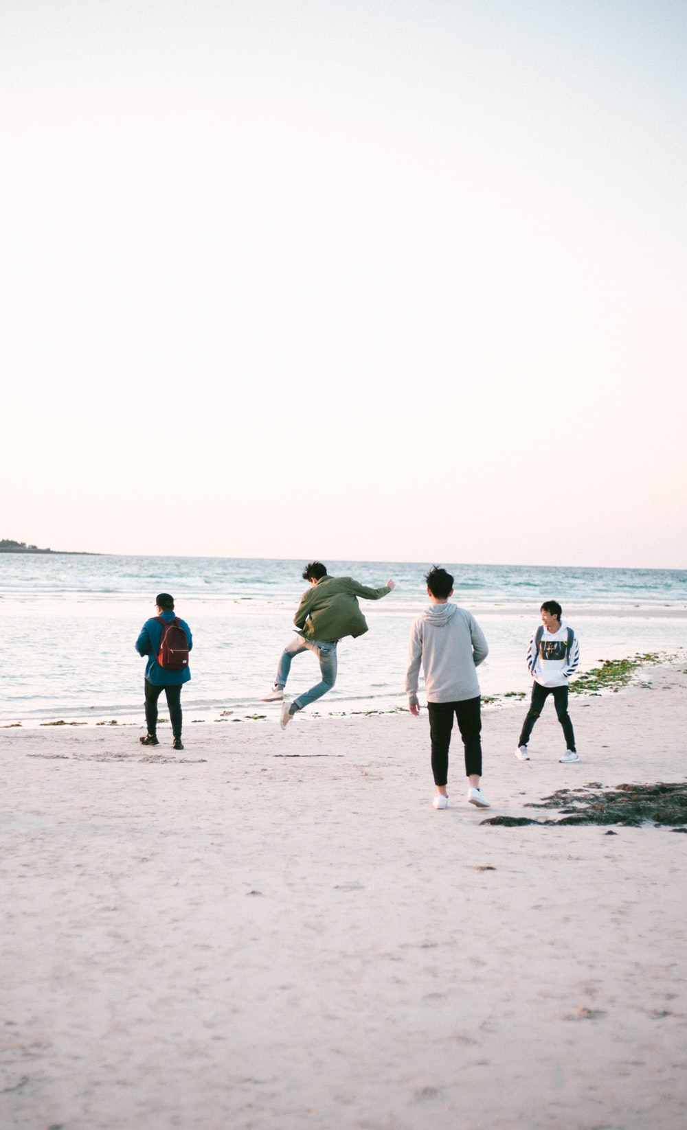 four persons near shore at daytime