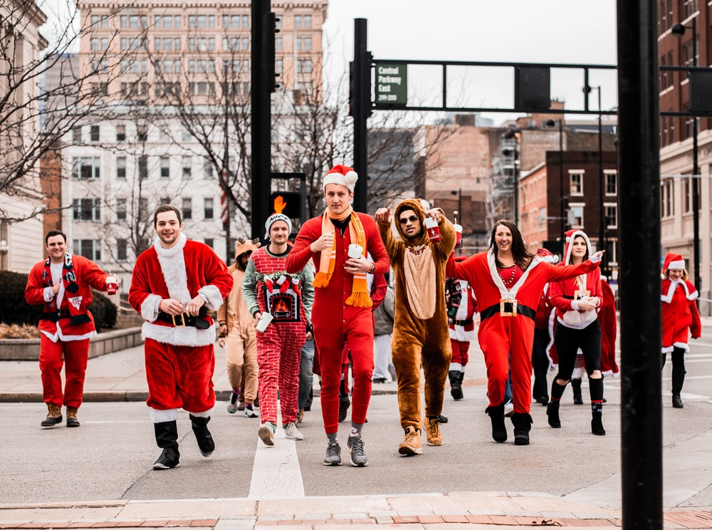 people in Santa Claus outfit marching down the street during daytime