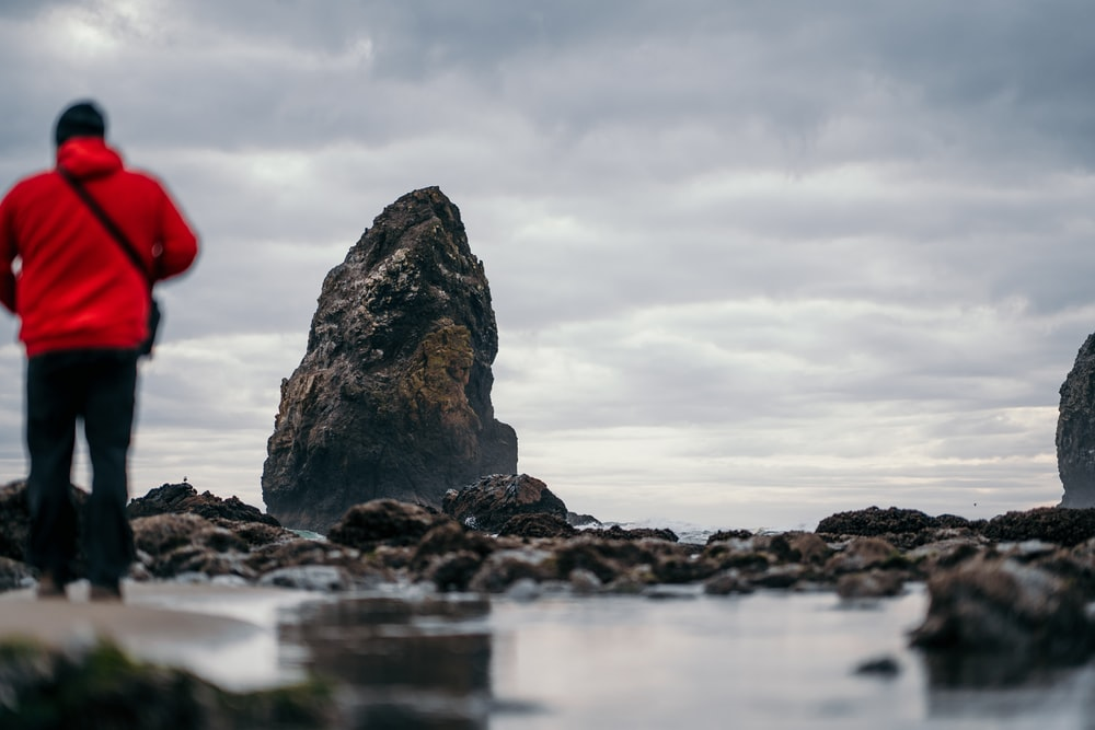 man in red hoodie standing on rocky shore under cloudy sky during daytime