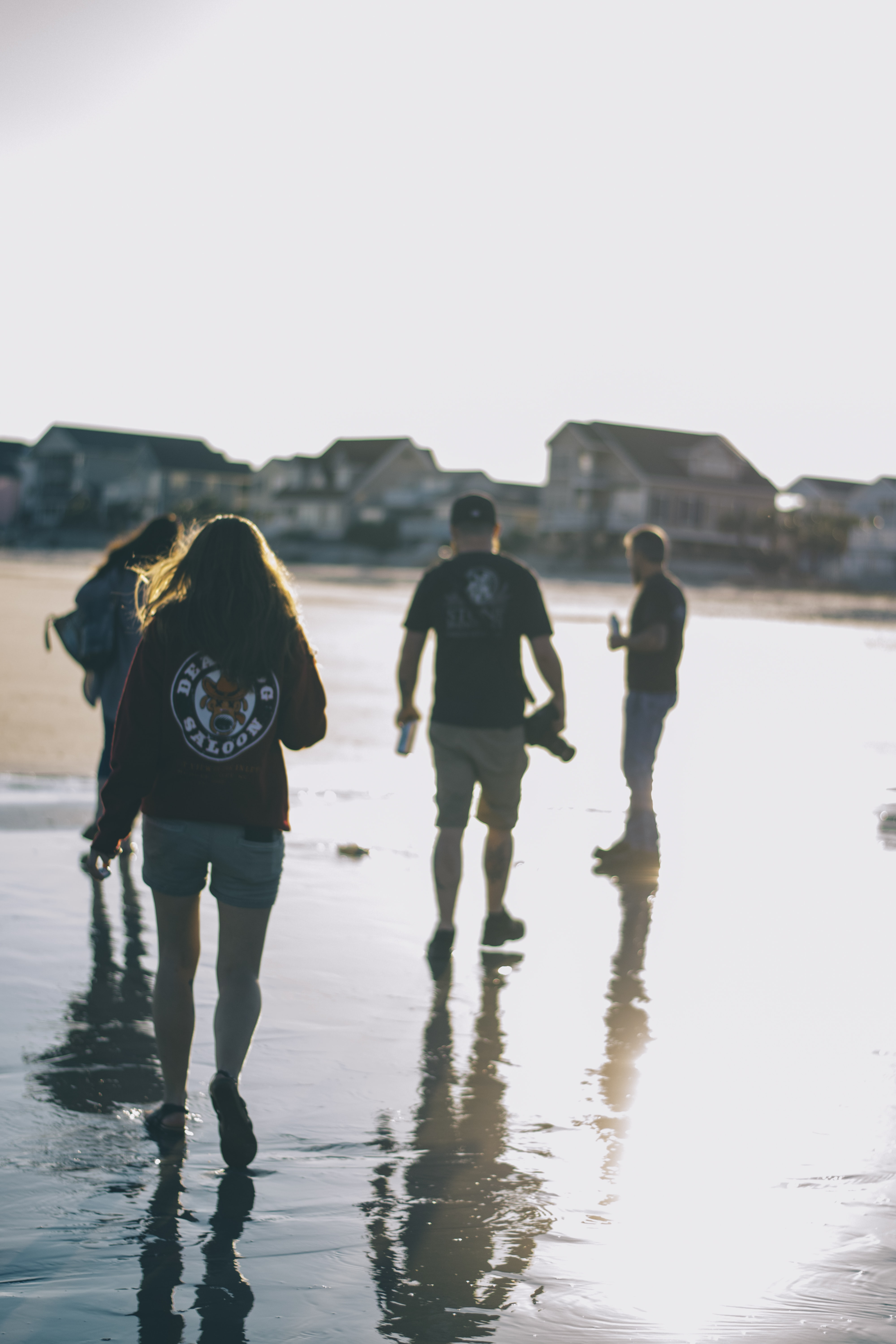 four people walking on wet ground