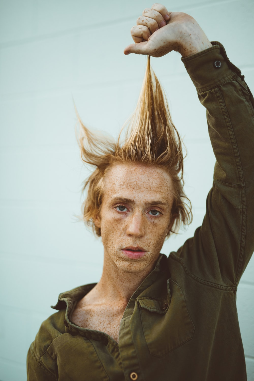 man pulling his hair up while standing near wall