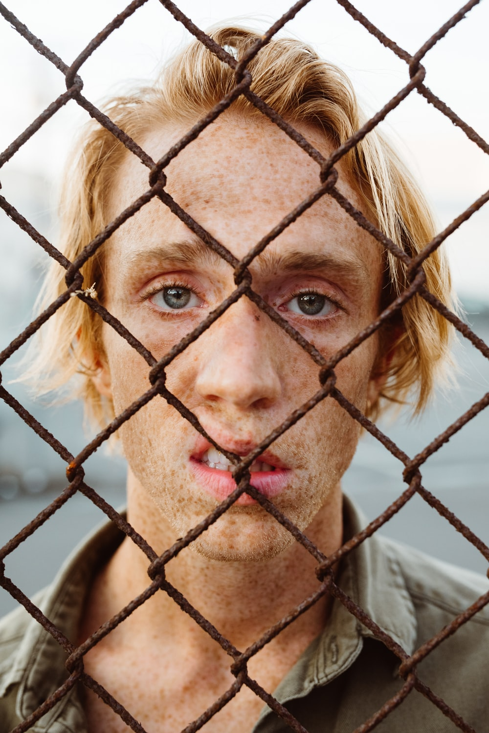 man in gray collared shirt standing behind chain link fence