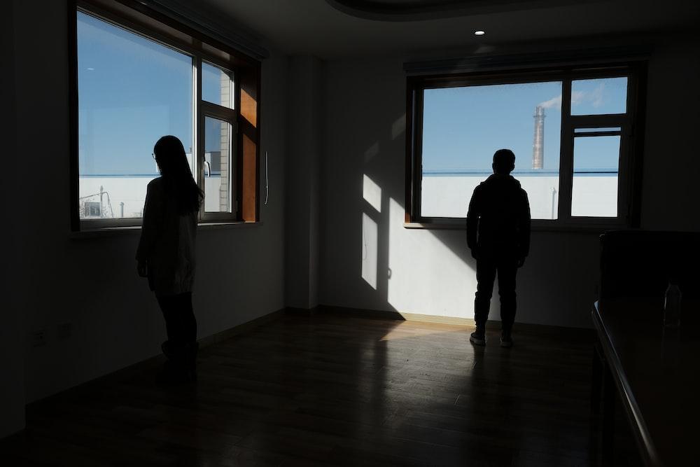 two people standing in dark room