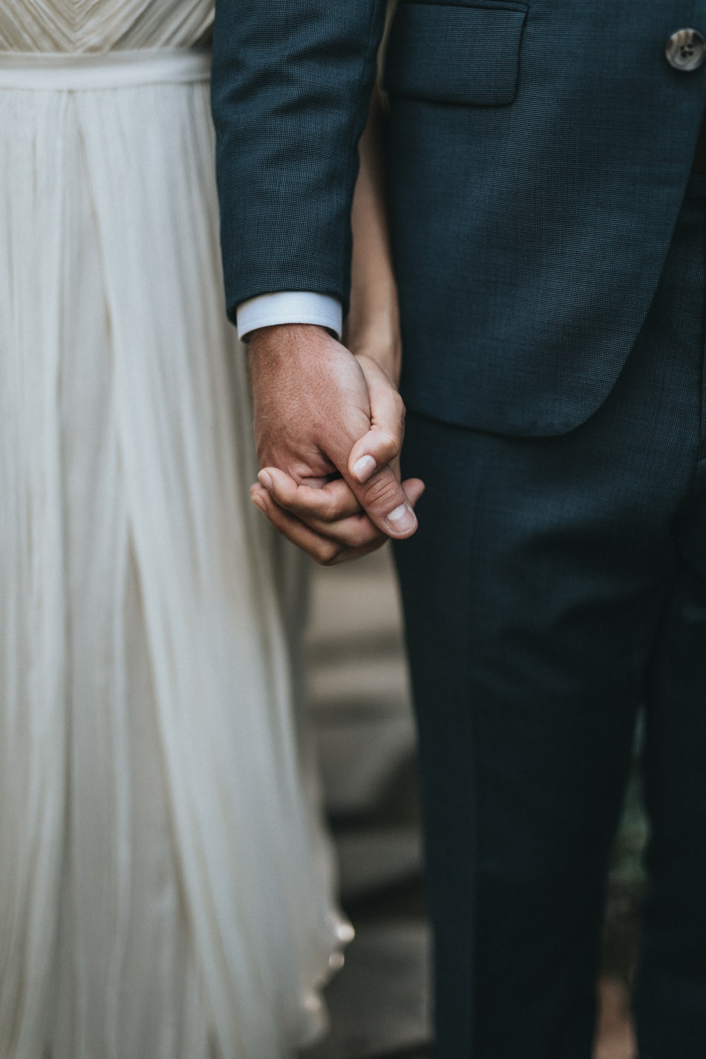 man in suit holding hands with woman in white skirt