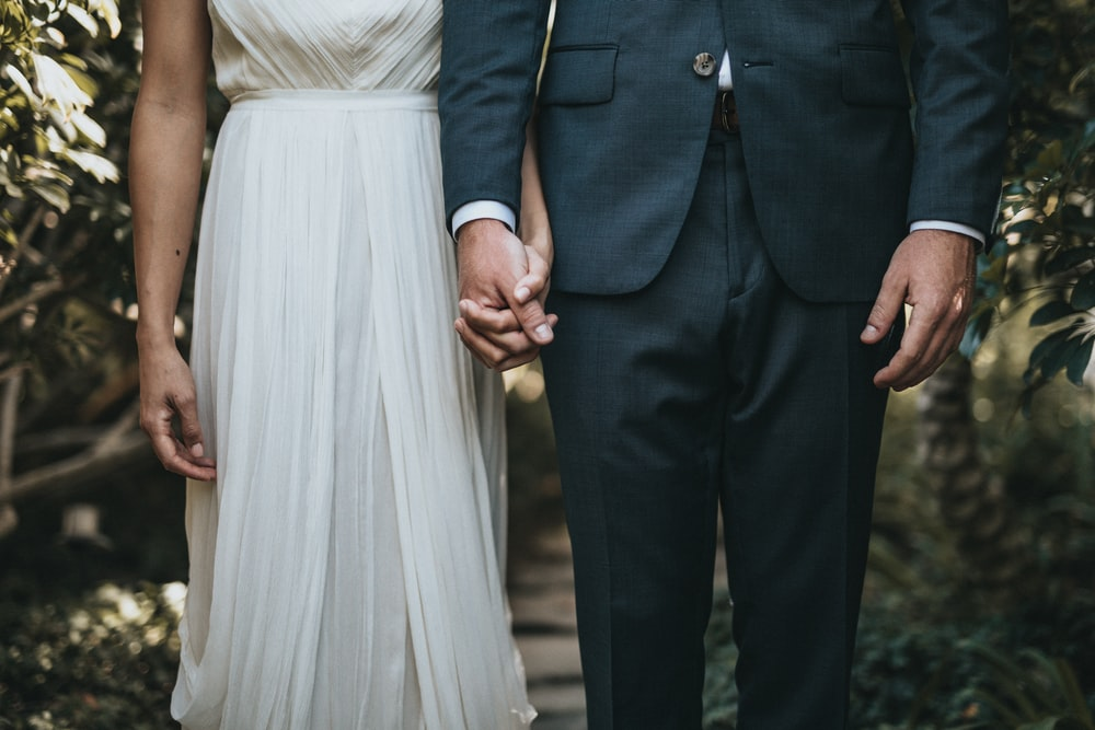 man in formal suit and woman in gray dress holding hands