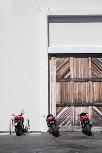 three black and red sports bike parked near gate