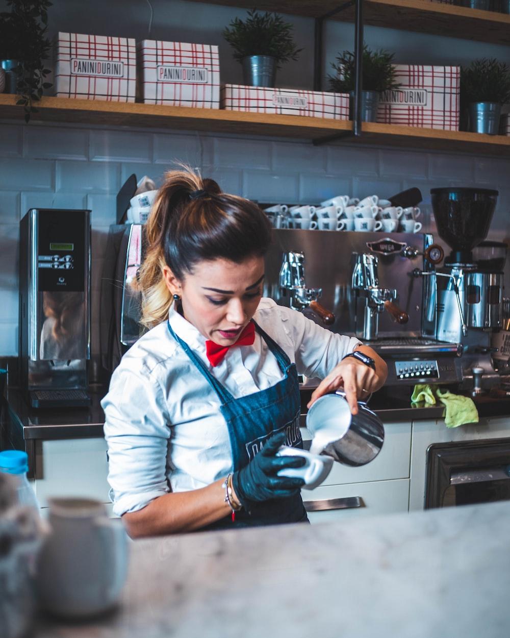 woman pouring liquid on mug