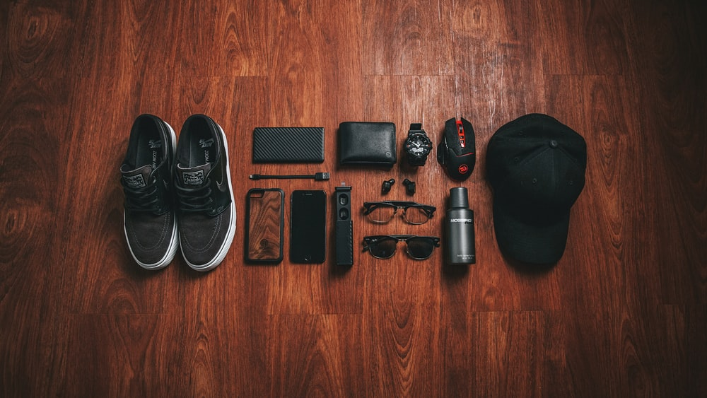 pair of black-and-white low-top sneakers beside black smartphone case
