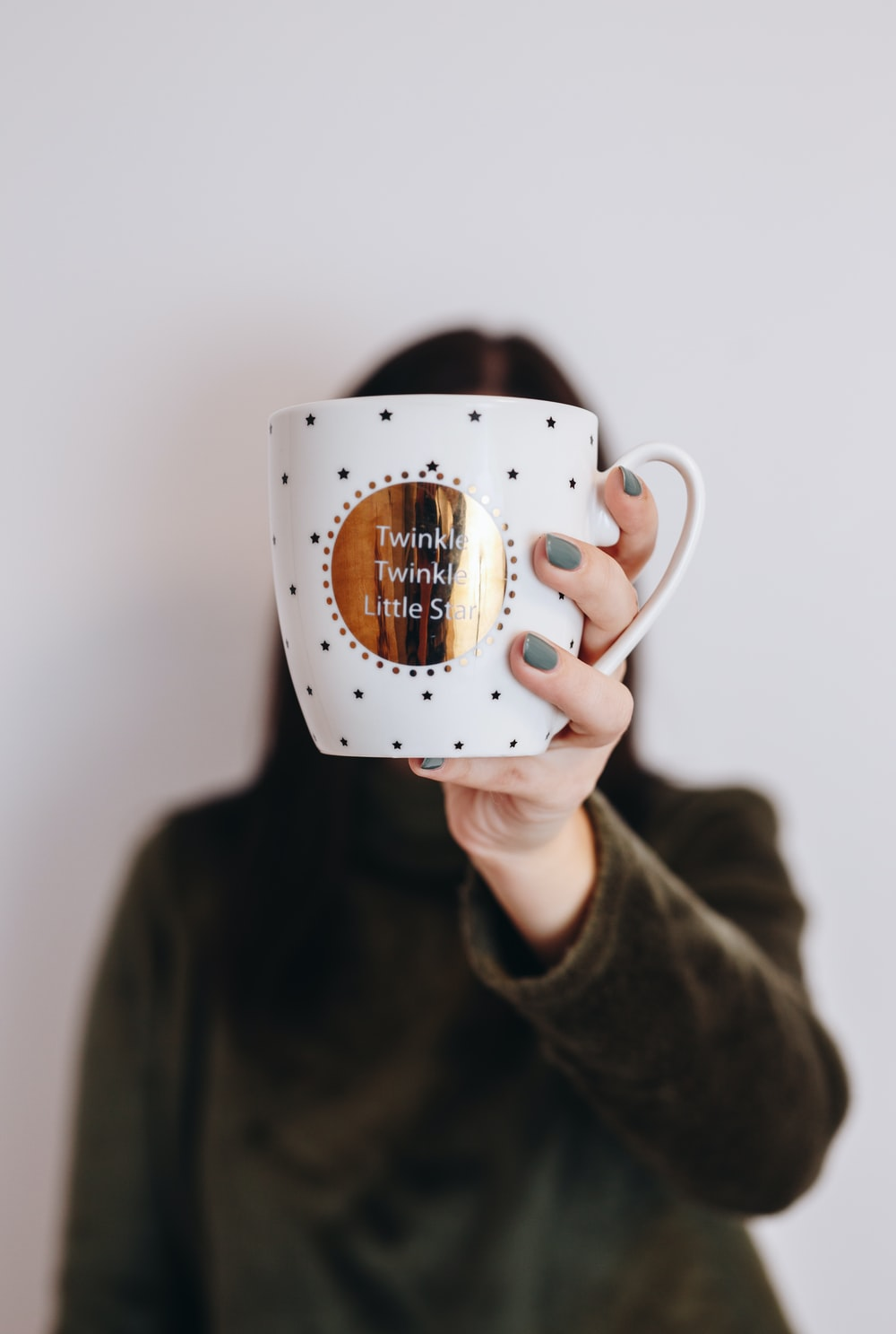 woman holding mug covering her face