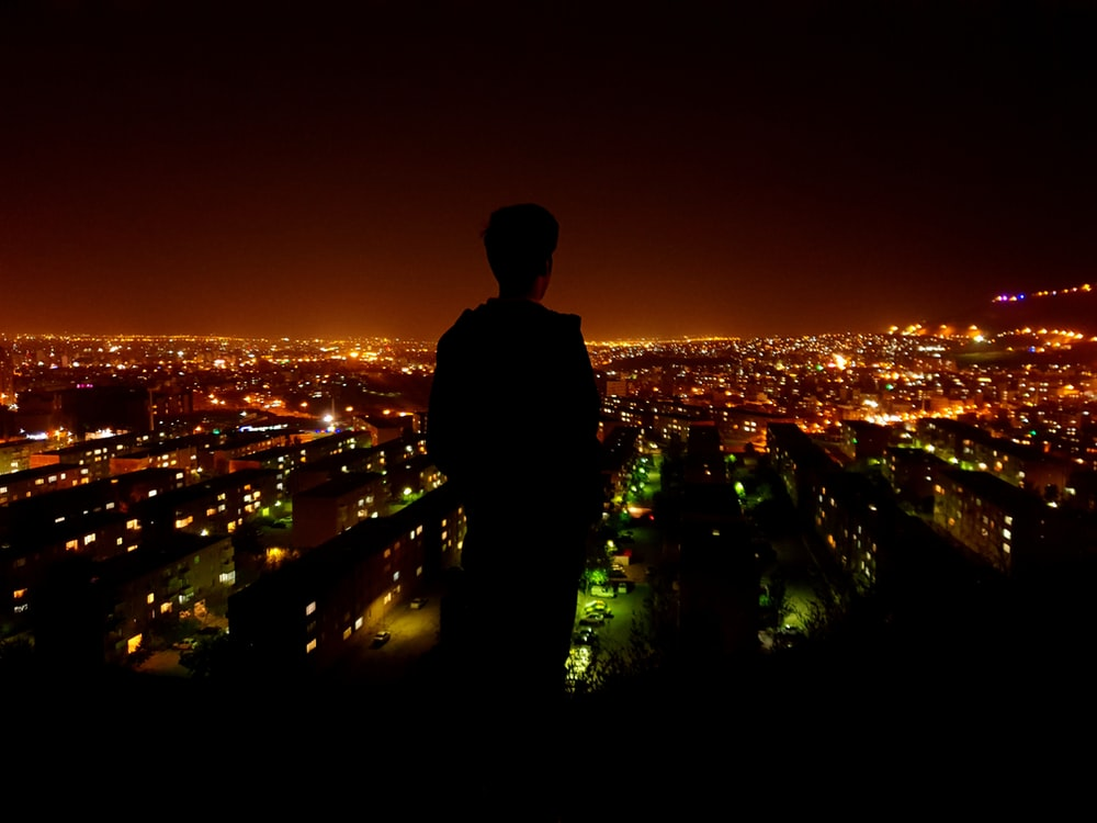 silhouette photo of person facing on lighted city