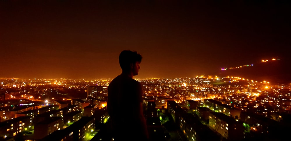 man standing looking at his right near city during night