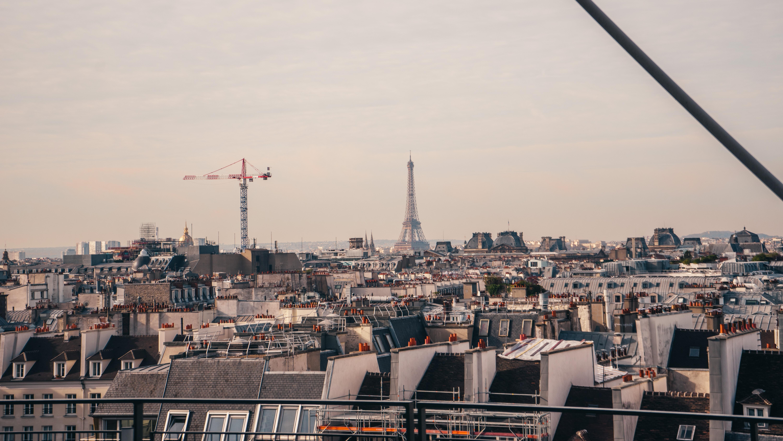 red and grey boom crane seen near Eiffel tower