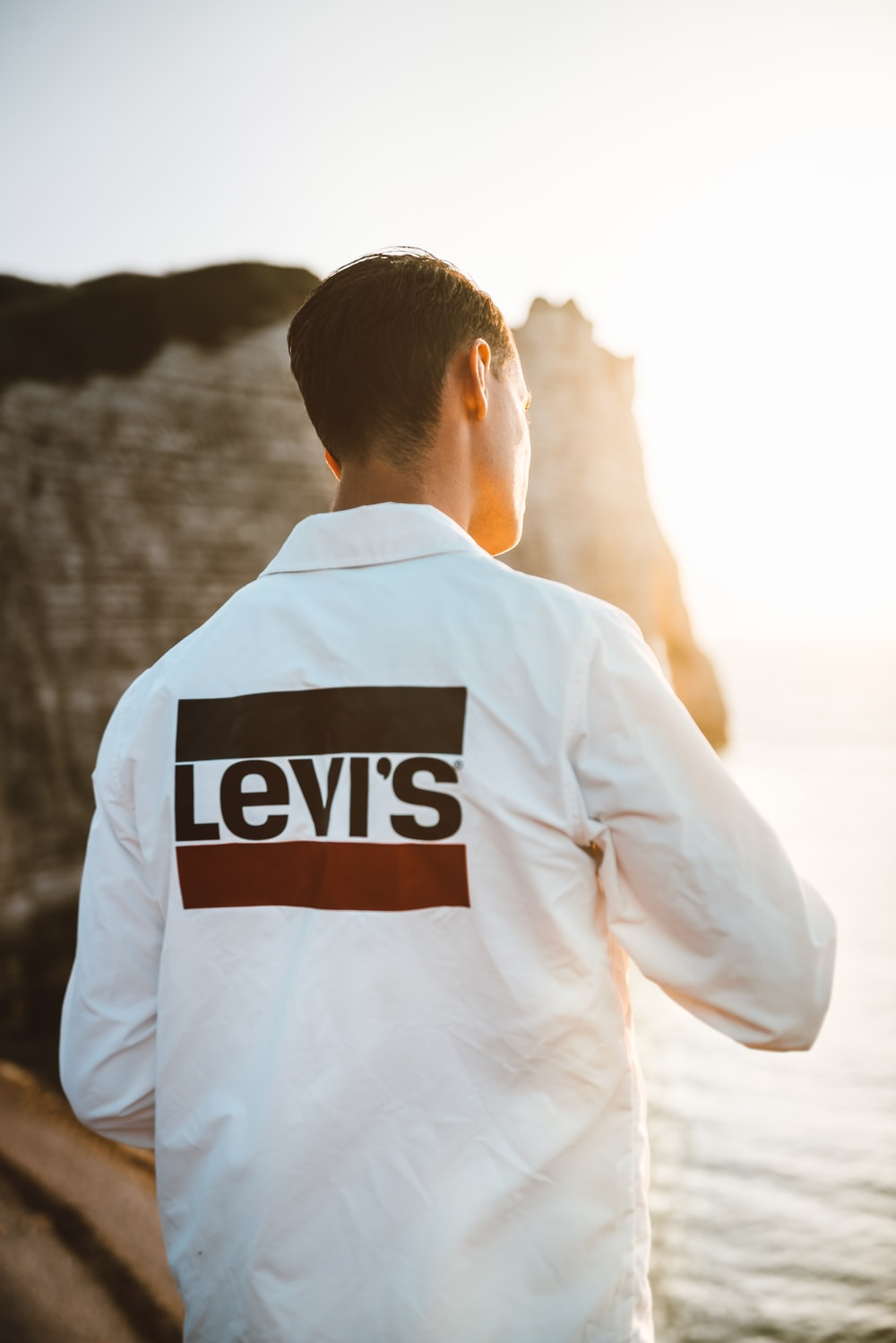 man wearing white Levi's shirt at the beach
