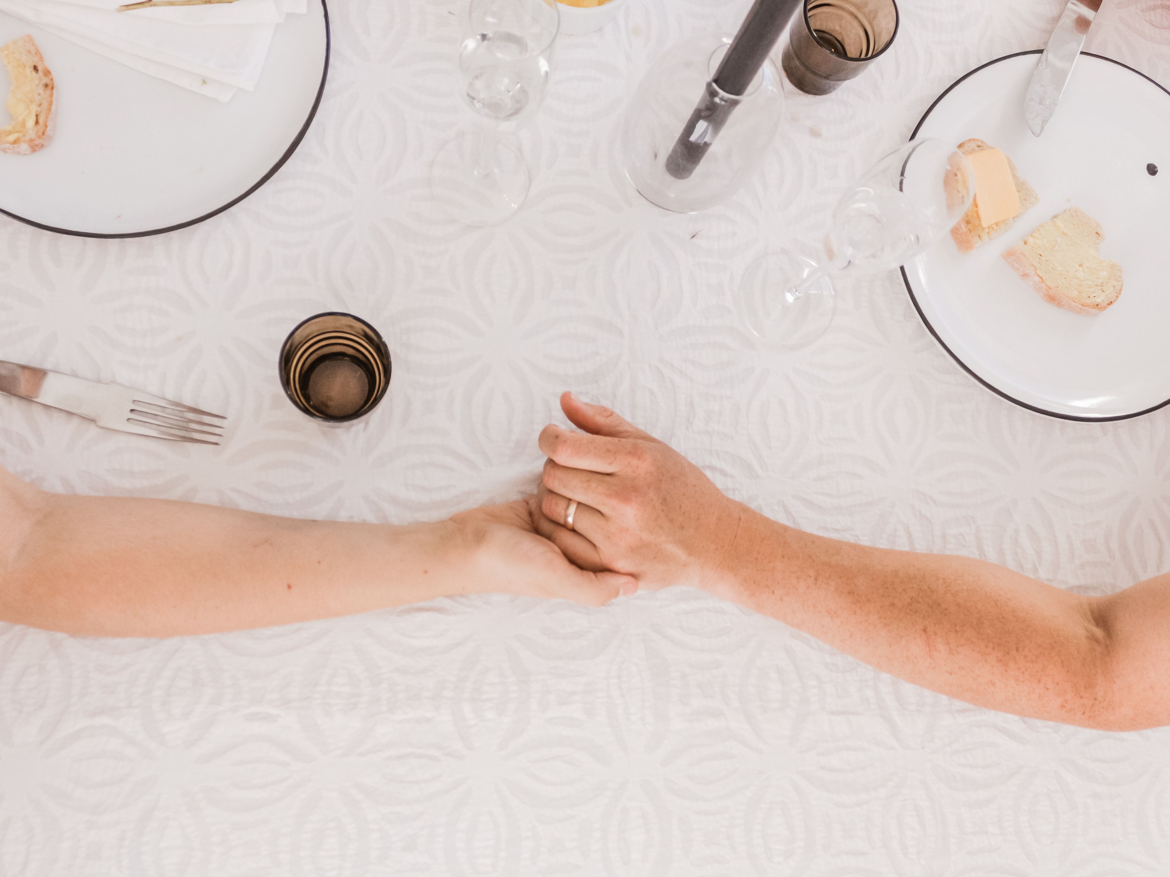 man and woman holding hands on tablecloth near plates and cups