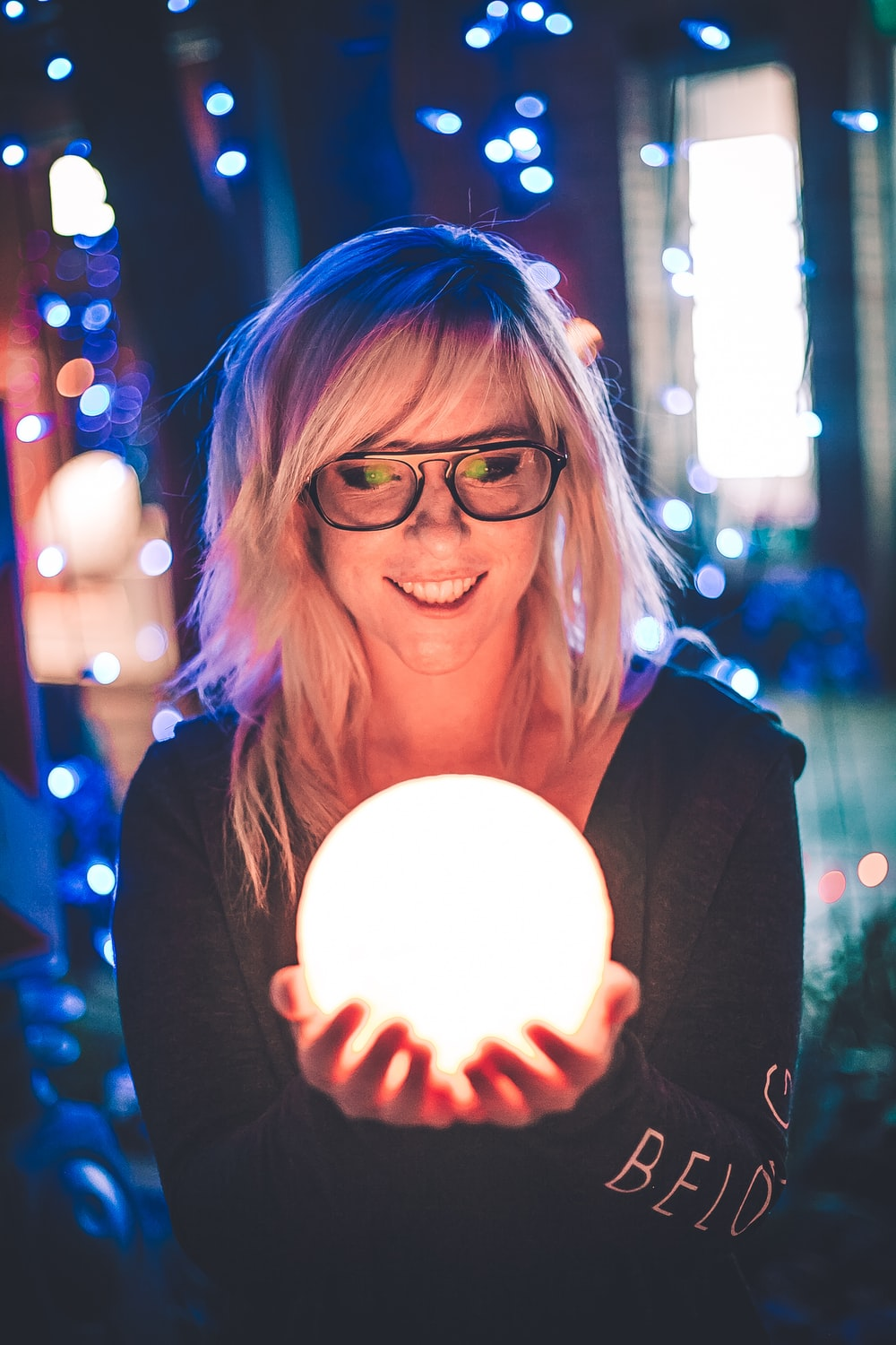 selective focus photography of woman holding lighted ball