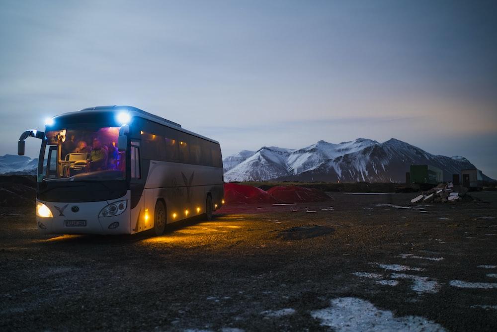 山の近くを走っている白と黒のバス