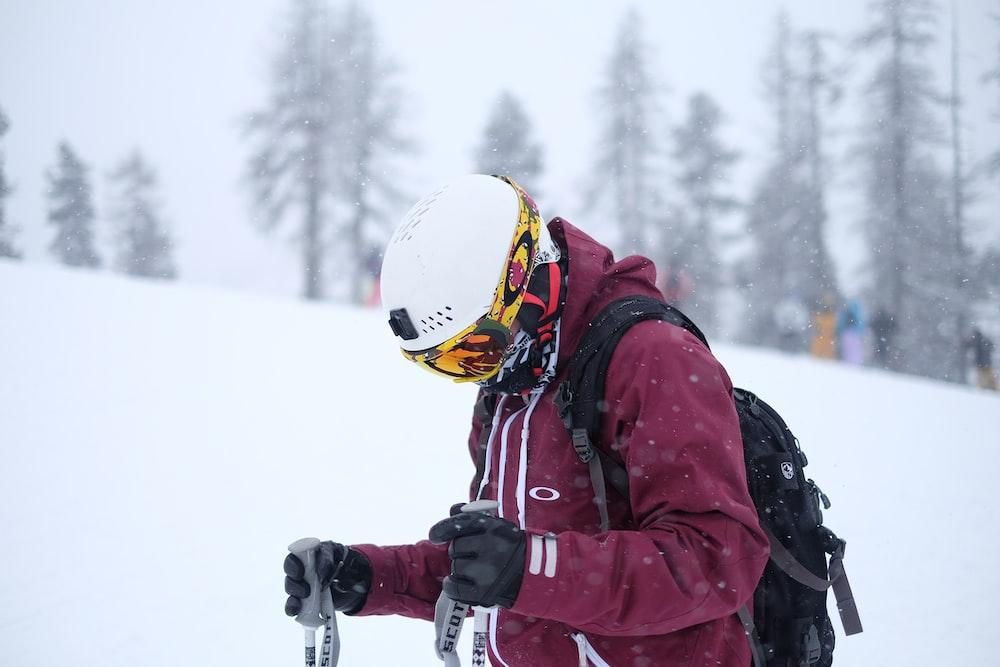 man wearing purple jacket and helmet holding ski poles on snow covered field
