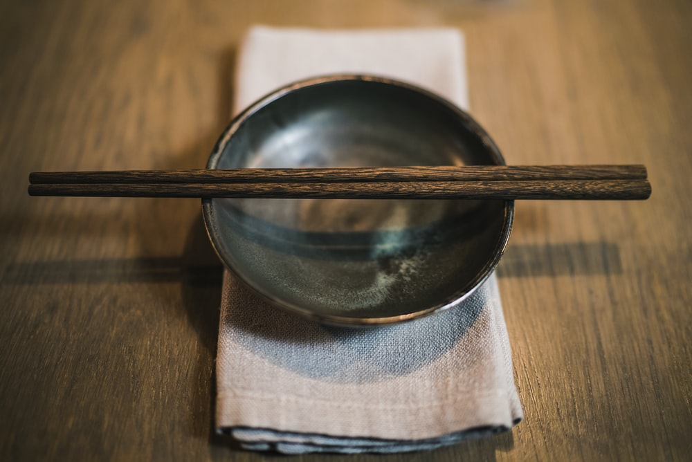 pair of brown chopsticks on round ceramic bowl