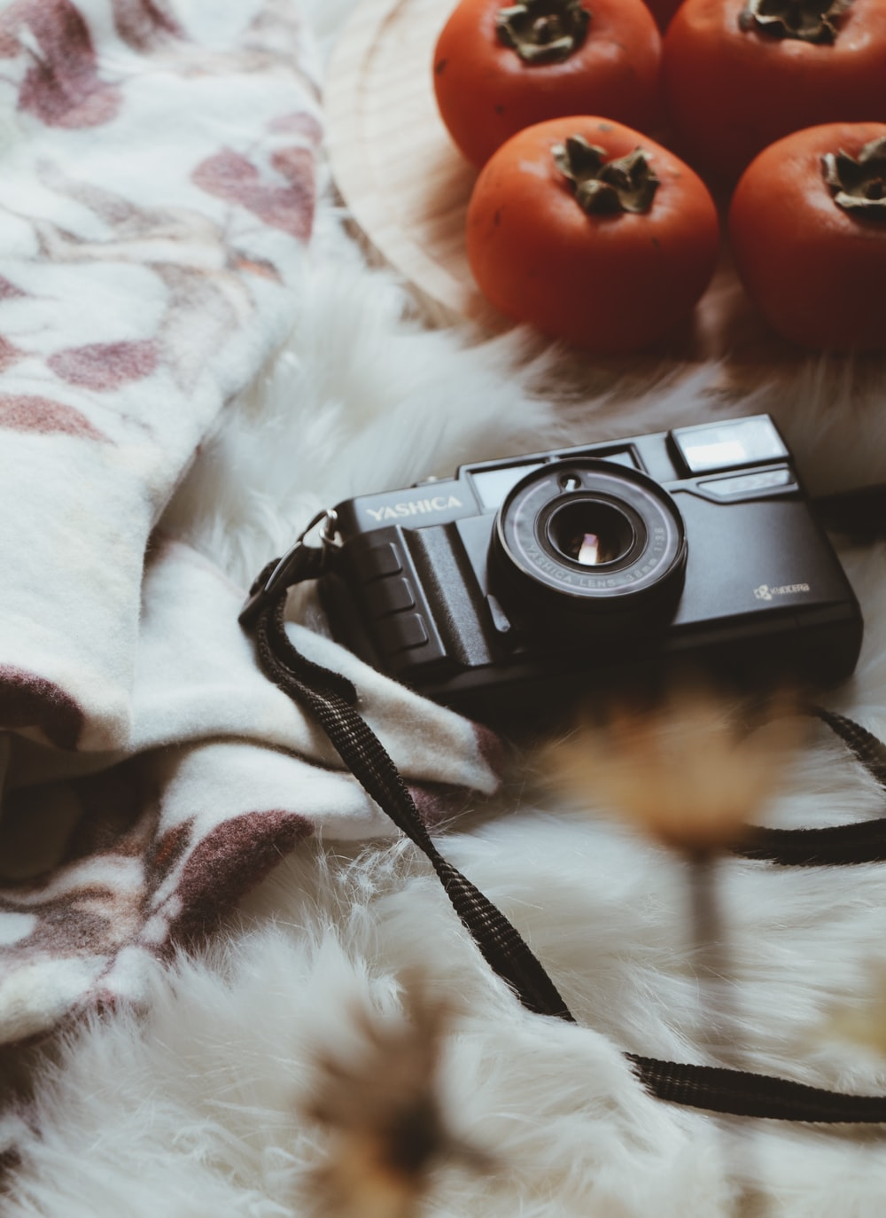 selective focus photo of black Yashica camera on white fur sheet