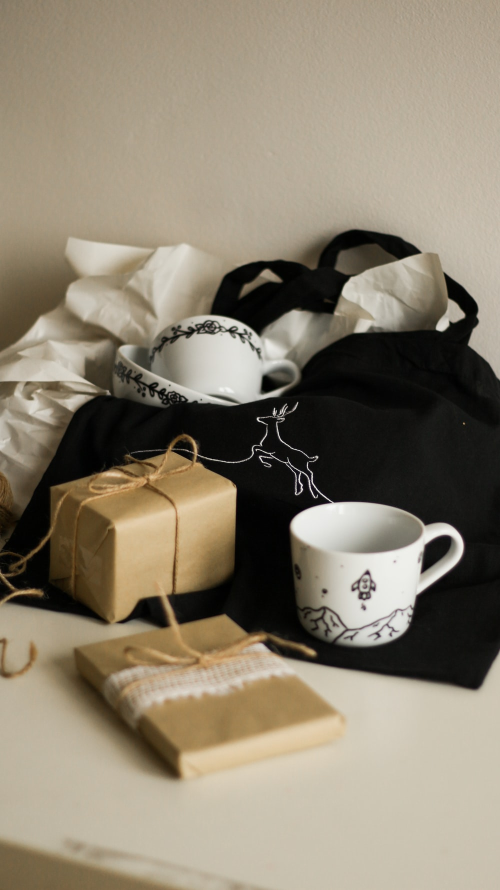 white ceramic mugs on black textile