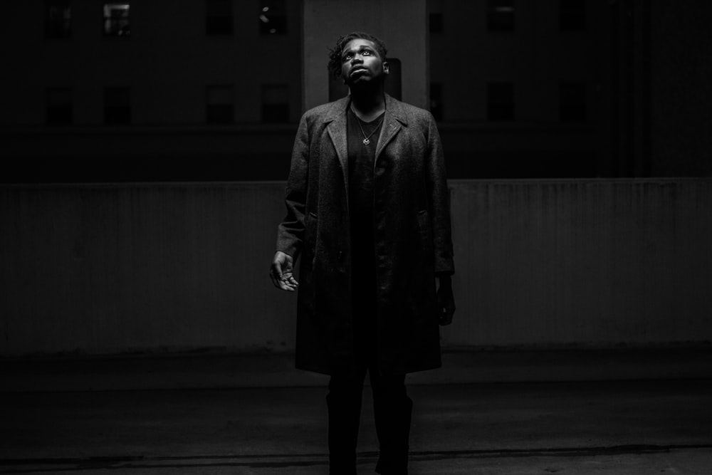grayscale photography of man standing wearing coat