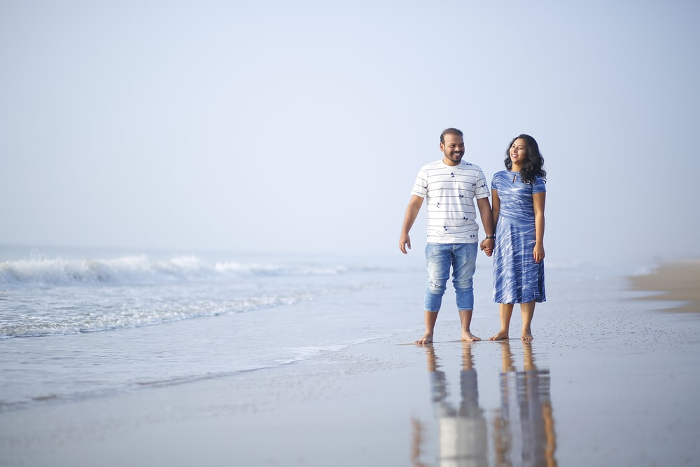 couple holding hands near shore