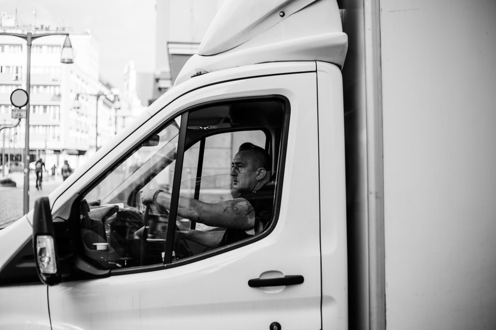 grayscale photography of man driving van