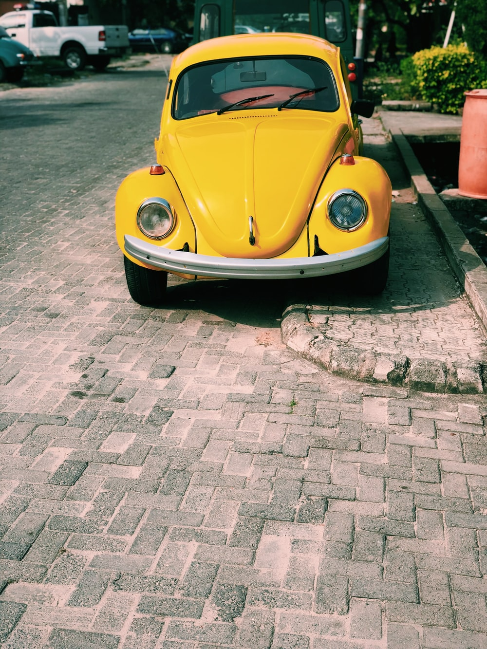 yellow Volkswagen Beetle coupe park outside during daytime