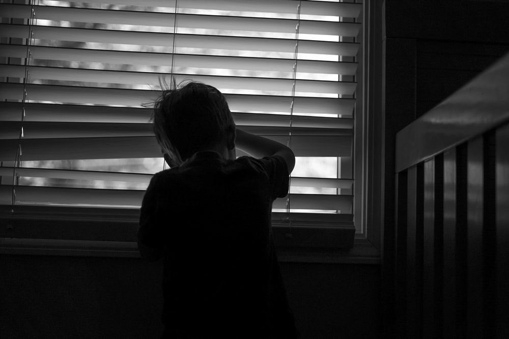 boy standing beside venetian blinds
